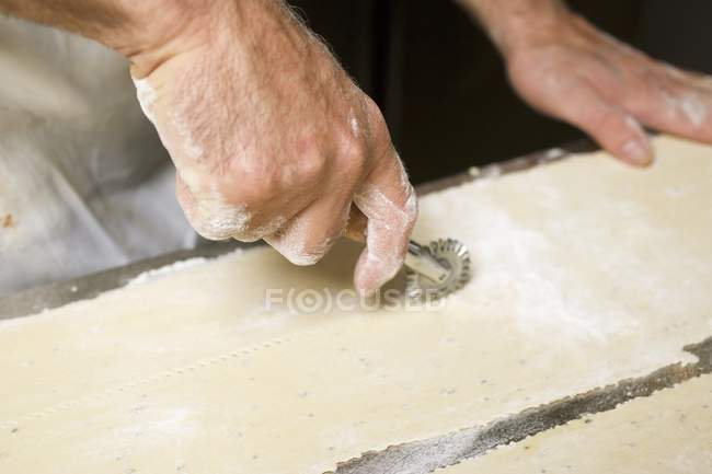 Cook cutting raw pasta dough — Stock Photo