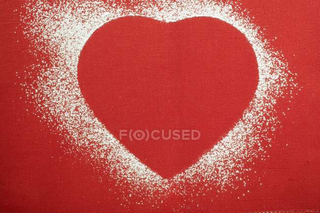 Red heart shape outlined in icing sugar — Stock Photo