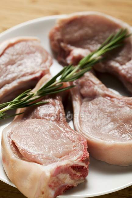 Raw pork chops with rosemary on plate — Stock Photo