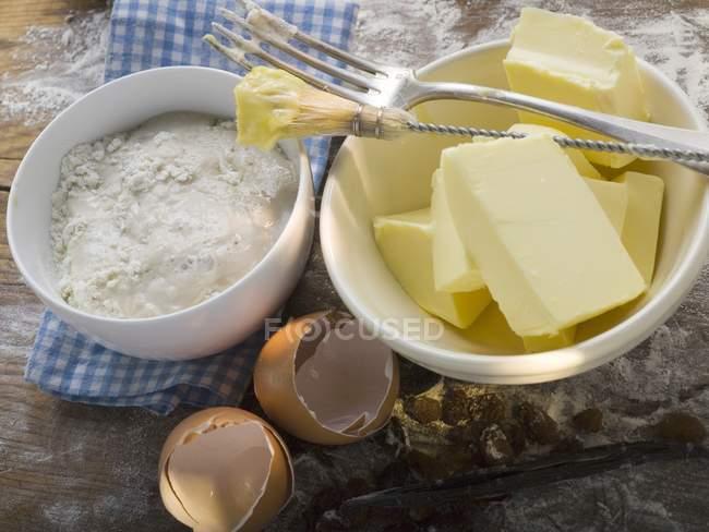 Vista de cerca de los ingredientes para hornear con cepillo de pastelería y tenedor - foto de stock
