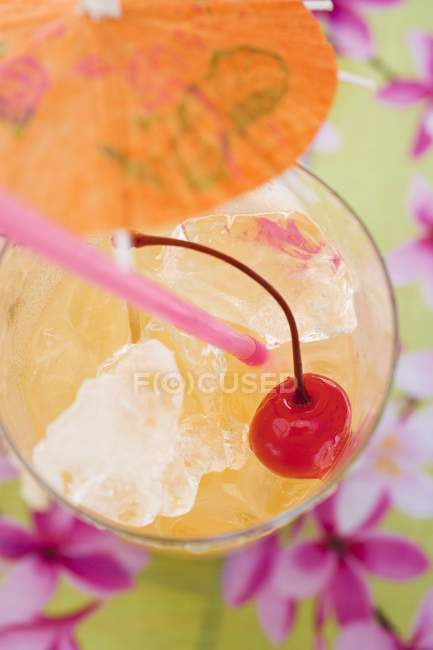 Closeup top view of fruity cocktail with ice cubes and cocktail cherry — Stock Photo