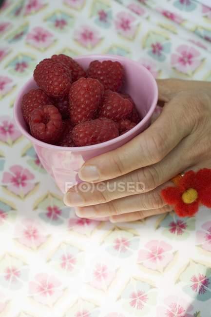 Female hand holding beaker with raspberries — Stock Photo