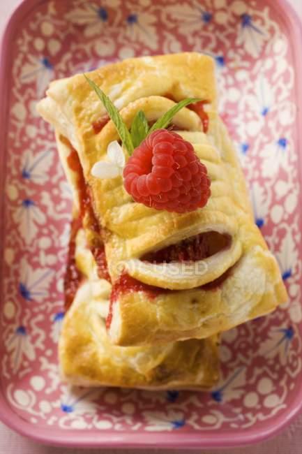 Vue rapprochée des pâtisseries empilées avec garniture framboise dans un plat à motifs — Photo de stock