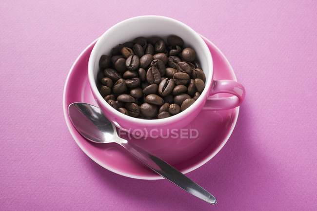 Coffee beans in pink coffee cup — Stock Photo
