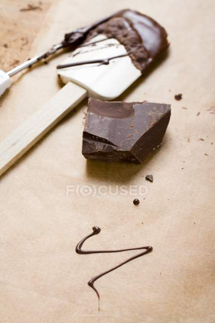 Pièce de chocolat sur surface en bois — Photo de stock