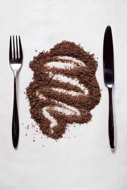 Vista de primer plano de chocolate rallado entre cuchillo y tenedor - foto de stock