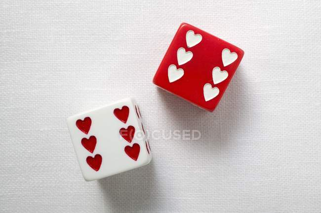 Closeup top view of two dice with hearts — color image, game