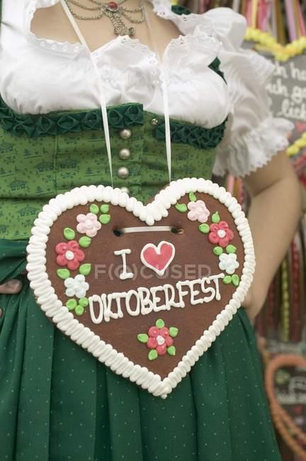 Vista cortada de mulher em vestido nacional com coração Lebkuchen — Fotografia de Stock