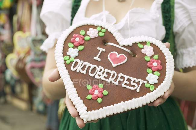 Vista cortada de mulher em vestido nacional segurando coração Lebkuchen — Fotografia de Stock