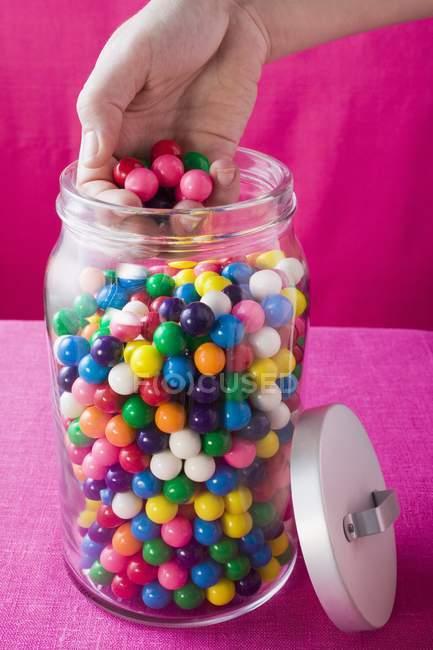 Recadrée vue de main sortir les boules de gomme couleur jar — Photo de stock