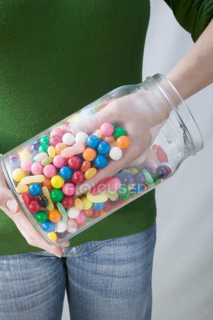 Recadrée vue de personne qui prend des boules de gomme couleur hors pot — Photo de stock