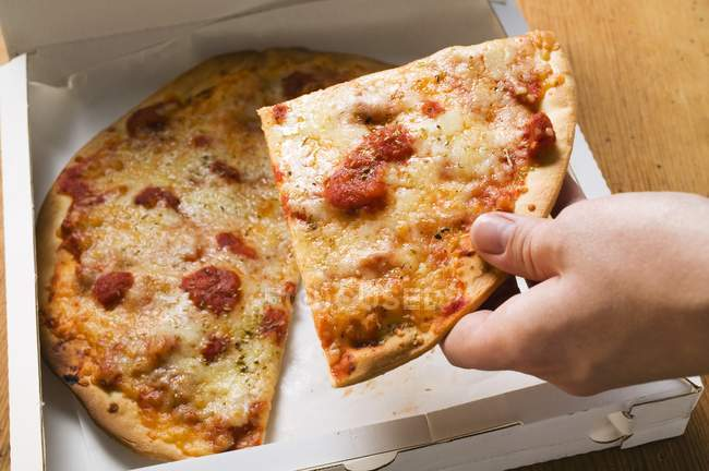 Hand taking slice of pizza — Stock Photo