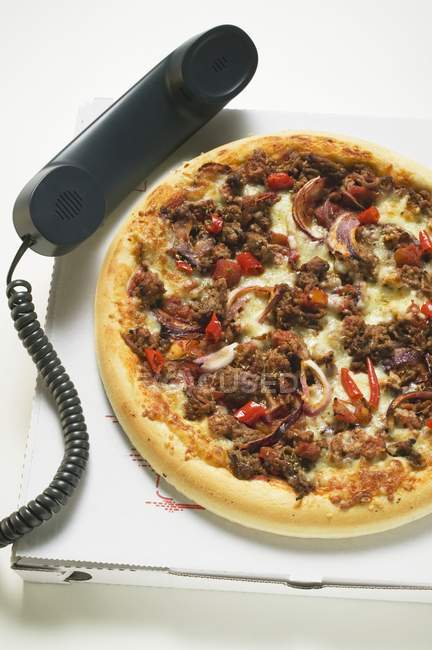 Pizza on box with telephone — Stock Photo