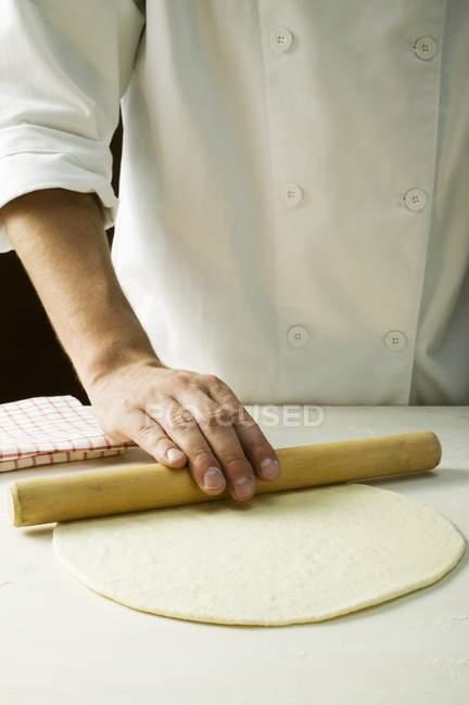Chef rolling pizza dough — Stock Photo