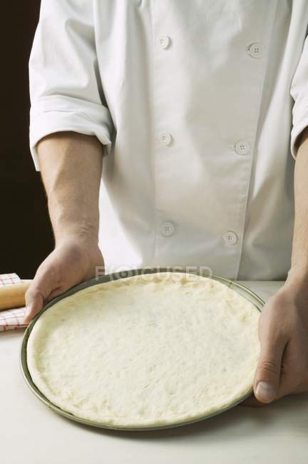 Chef holding pizza dough — Stock Photo