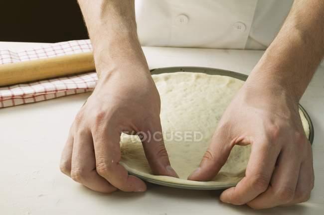 Chef pressing pizza dough — Stock Photo