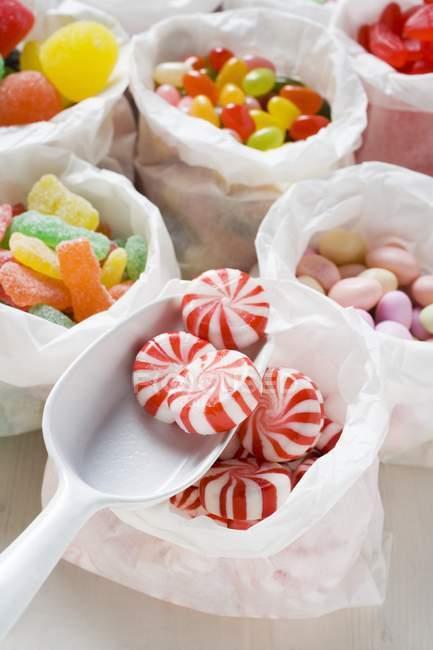 Dulces surtidos en bolsas de papel - foto de stock