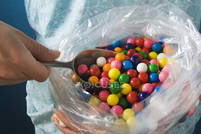 Vue recadrée de personne qui prend des boules de gomme de sac en plastique avec boule — Photo de stock