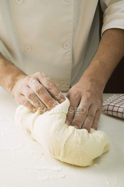 Chef kneading pizza dough — Stock Photo