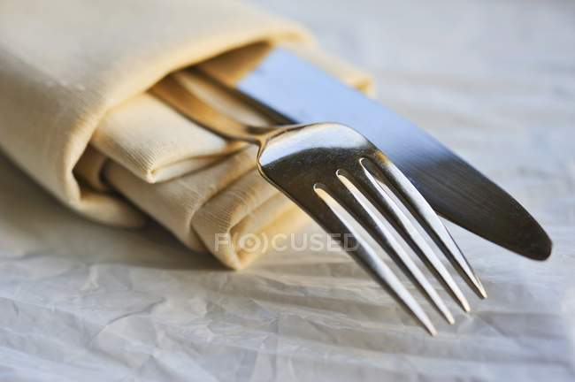 Closeup view of fabric serviette with knife and fork — Stock Photo