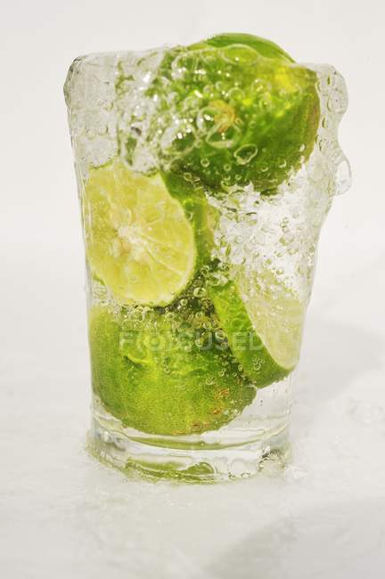 Sliced Limes in glass of water — Stock Photo