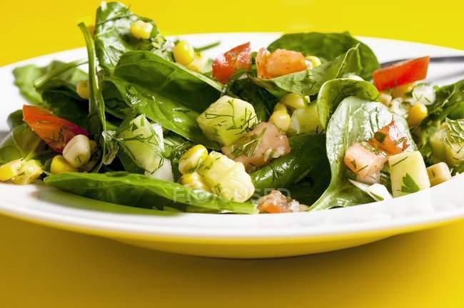 Ensalada de espinacas y maíz dulce con tomates, pepino y eneldo en plato blanco - foto de stock