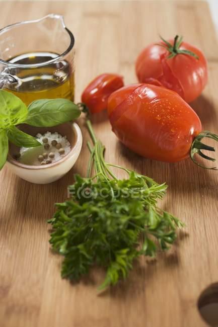 Інгредієнти для томатному соусі: помідори, трави, оливкова олія, спеції над деревної поверхні — стокове фото