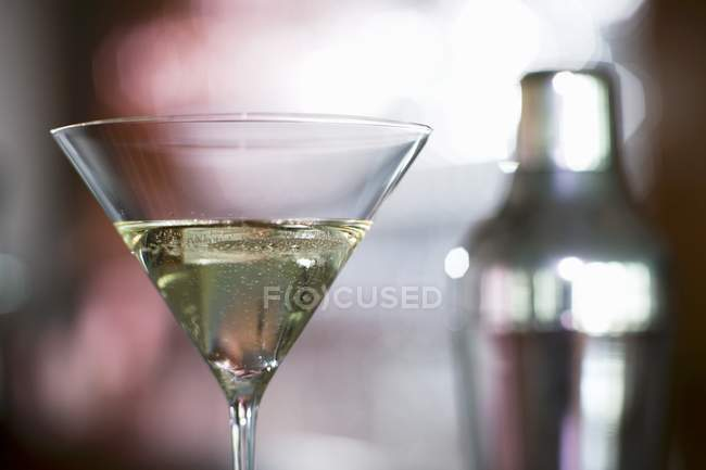 Closeup view of cocktail glass with cocktail shaker on background — Stock Photo