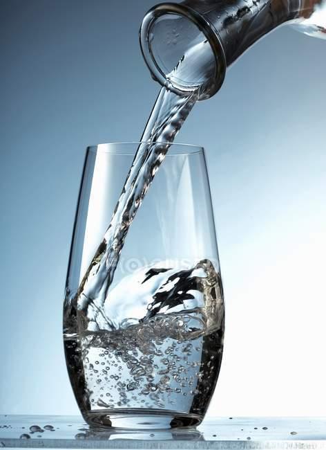 Gießen von Wasser in Glas — Stockfoto