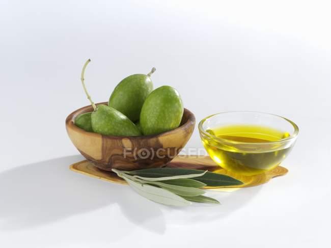 Оливки зелёные с оливковыми листьями и нефти — стоковое фото