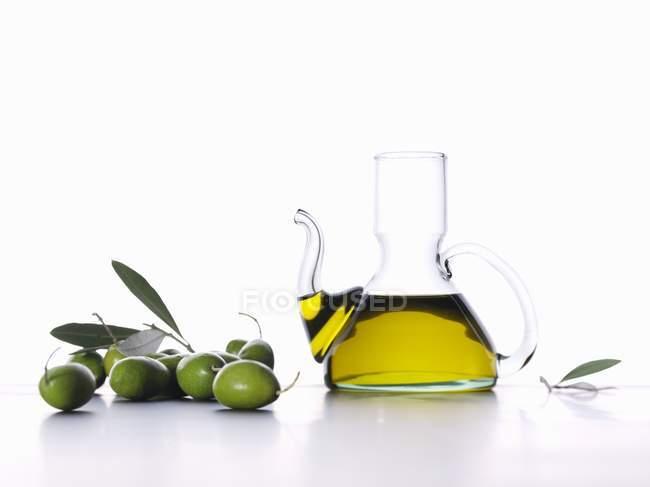 Оливковое масло в графин с зелеными оливками — стоковое фото