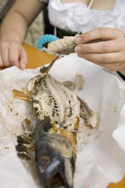 Femme mangeant du poisson sur bâton — Photo de stock