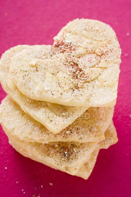 Gros plan vue du dessus des biscuits empilés en forme de coeur d'amande avec du sucre — Photo de stock