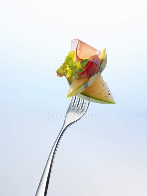 Melão com alface e presunto em garfo — Fotografia de Stock
