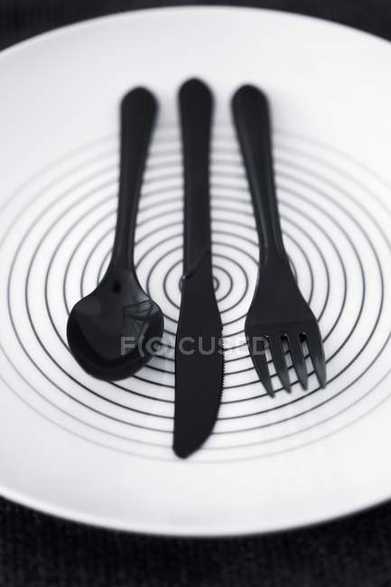Closeup view of black plastic cutlery on a plate — Stock Photo