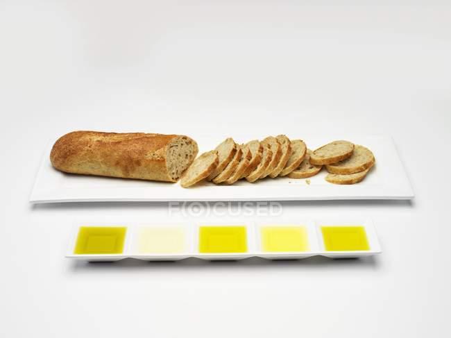 Bodegón con baguette en rodajas y varios tipos de aceite de oliva para degustar - foto de stock
