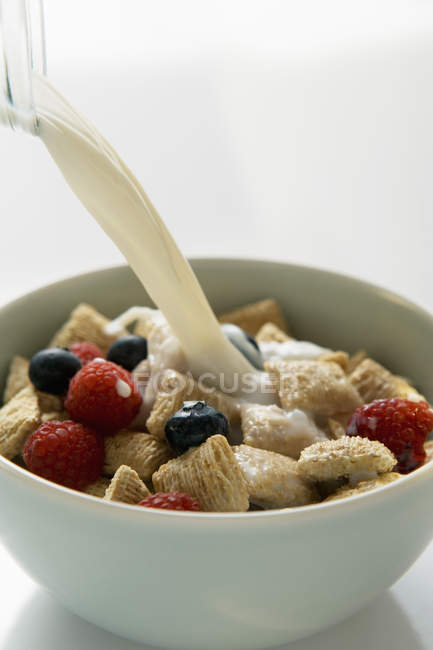 Pouring milk over cereal — Stock Photo