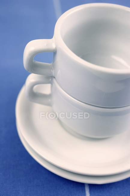 Closeup view of two empty Espresso cups with saucers in a pile — Stock Photo