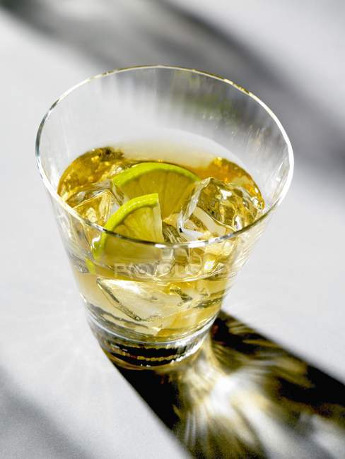 Closeup view of drink with ice cubes and slices of lime — Stock Photo