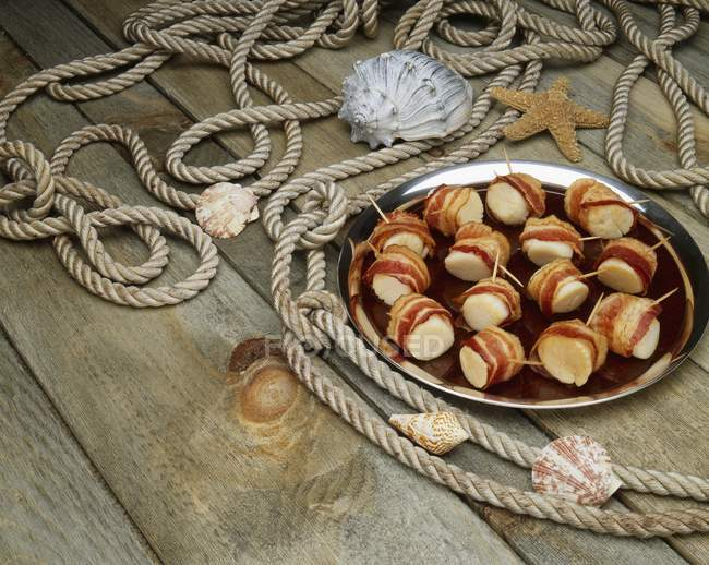 Elevated view of bacon wrapped scallops on wooden planks with rope and shells — Stock Photo