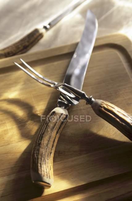 Vista de cerca de asta de Ciervo tallado juego sobre tablero de madera - foto de stock