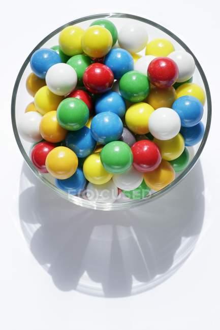 Primer plano vista superior de bolas de goma de mascar de colores en tazón de vidrio - foto de stock
