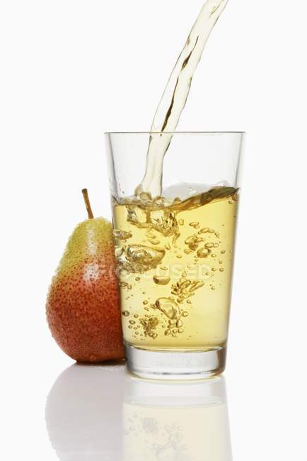 Pouring pear juice into glass — Stock Photo