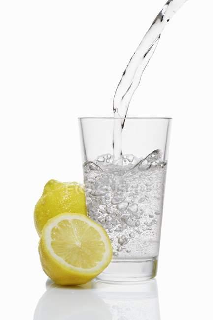 Vaso de limonada en una taza transparente con un batiburrillo. - foto de stock