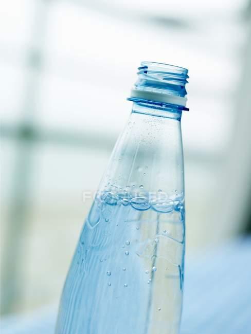 Vista de perto de água mineral em garrafa de plástico aberta — Fotografia de Stock