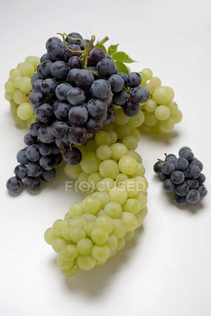 Bunches of green and black grapes — Stock Photo