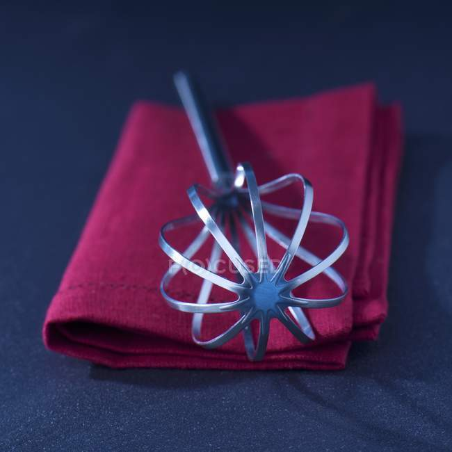 Closeup view of a one whisk on a red towel — Stock Photo