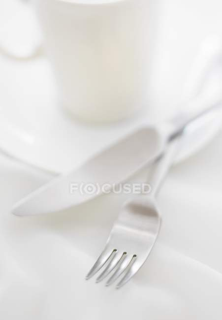 Closeup view of fork and knife near white cup and saucer — Stock Photo