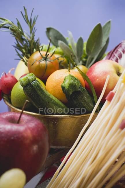 Fresh vegetables, fruits and spaghetti pasta — Stock Photo