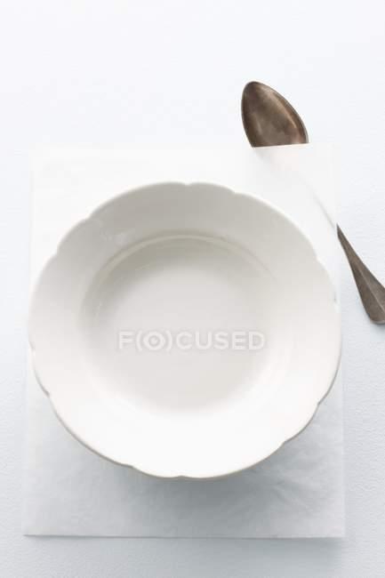 Detalle vista superior de un plato blanco vacío en un pedazo de papel con una cuchara - foto de stock
